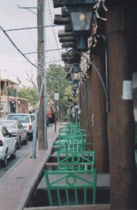 Green chairs at a streetside cafe